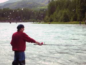 Travis fishing with brown bear across river